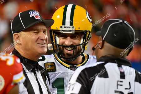 Green Bay Packers quarterback Aaron Rodgers jokes with line judge Mark Perlman, left, and field judge Mearl Robinson (31), before an NFL football game against the Kansas City Chiefs in Kansas City, Mo