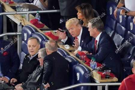 President Donald Trump, center, leans over to talk with Republican lawmakers from l-r, Rep. Andy Biggs, R-Ariz., Rep. Mark Meadows, R-N.C., Sen. Lindsey Graham, R-S.C., and Sen. David Perdue, R-Ga., during Game 5 of baseball World Series between the Houston Astros and Washington Nationals, at Nationals Park in Washington. Sitting directly behind the President is first lady Melania Trump