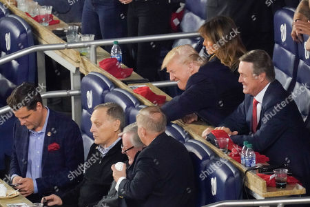 President Donald Trump, top right, leans over to pass a baseball while talking with Republican lawmakers from l-r, Rep. Matt Gaetz, R-Fla., Rep. Andy Biggs, R-Ariz., Rep. Mark Meadows, R-N.C., Sen. Lindsey Graham, R-S.C., and Sen. David Perdue, R-Ga., during Game 5 of baseball World Series between the Houston Astros and Washington Nationals, at Nationals Park in Washington. Sitting directly behind the President is first lady Melania Trump
