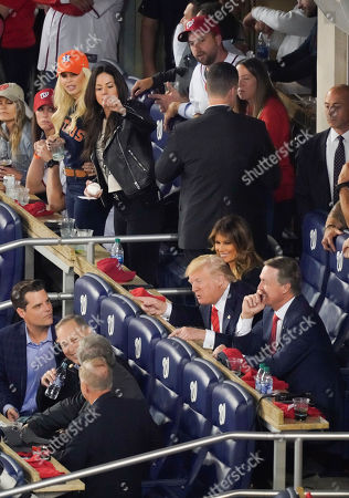 President Donald Trump, right, talking with Republican lawmakers from l-r, Rep. Matt Gaetz, R-Fla., Rep. Andy Biggs, R-Ariz., Rep. Mark Meadows, R-N.C., Sen. Lindsey Graham, R-S.C., and Sen. David Perdue, R-Ga., during Game 5 of baseball World Series between the Houston Astros and Washington Nationals, at Nationals Park in Washington. Sitting directly behind the President is first lady Melania Trump