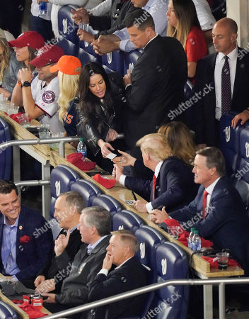 President Donald Trump, center, is handed card by an unknown woman from adjoining suite while seated with Republican lawmakers from l-r, Rep. Matt Gaetz, R-Fla., Rep. Andy Biggs, R-Ariz., Rep. Mark Meadows, R-N.C., Sen. Lindsey Graham, R-S.C., and Sen. David Perdue, R-Ga., during Game 5 of baseball World Series between the Houston Astros and Washington Nationals, at Nationals Park in Washington. Sitting directly behind the President is first lady Melania Trump