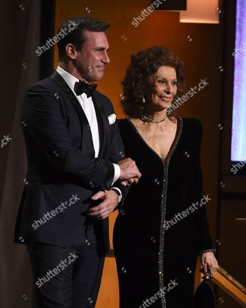 Jon Hamm, Sophia Loren. Jon Hamm, left, and Sophia Loren walk on stage to present an award. at the Governors Awards, at the Dolby Ballroom in Los Angeles