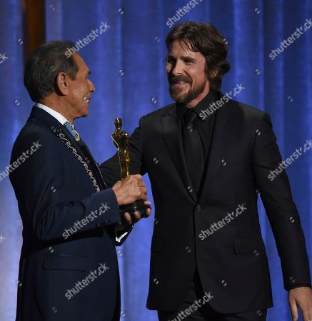 Christian Bale, Wes Studi. Christian Bale, right, presents an honorary award to Wes Studi at the Governors Awards, at the Dolby Ballroom in Los Angeles