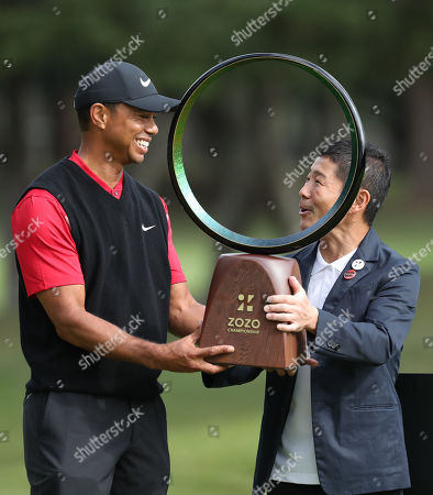 Tiger Woods (L) of the United States receives the trophy from former CEO and founder of Zozo, Yusaku Maezawa (R), after reaching all-time record of 82 wins of the PGA tour at the final round of Zozo Championship PGA tour at the Accordia Golf Narashino Country Club course in Inzai, Chiba Prefecture, 28 October 2019. Woods reached 82 wins of PGA tour and tied the career record held by Sam Snead. The final round was suspended on 27 October due to darkness.