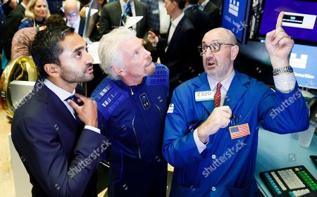 Sir Richard Branson (C), the founder of Virgin Galactic, and Chamath Palihapitiya (L), the founder of Social Capital Hedosophia, talk with specialistPeter Giacchi (R) at the New York Stock Exchange before celebrating the first day of trading of Virgin Galactic Holdings shares in New York, New York, USA, on 28 October 2019. The commercial space travel and exploration company is a result of the merger of Virgin Galactic and Social Capital Hedosophia.