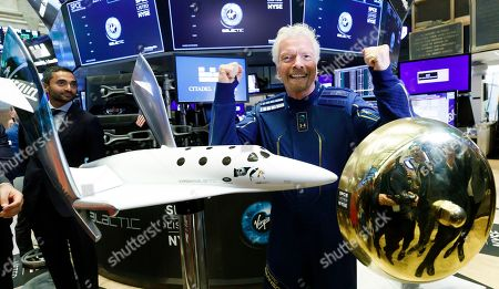 ]Sir Richard Branson (C), the founder of Virgin Galactic, poses with a ceremonial bell and a spaceship model at the New York Stock Exchange to celebrate the first day of trading of Virgin Galactic Holdings shares in New York, New York, USA, on 28 October 2019. The commercial space travel and exploration company is a result of the merger of Virgin Galactic and Social Capital Hedosophia.