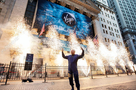 Sir Richard Branson, founder of Virgin Galactic, poses for a photo outside the New York Stock Exchange as fireworks are exploded before his company's IPO