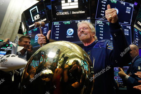 Sir Richard Branson, founder of Virgin Galactic, poses for photos after ringing a ceremonial bell on the floor of the New York Stock Exchange, as his company's stock opens for trading