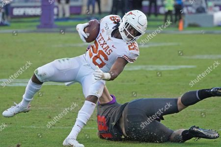 Stock Photo of Keaontay Ingram, Ben Wilson. Texas running back Keaontay Ingram (26) runs the ball as TCU linebacker Ben Wilson (18) defends in the second half of an NCAA college football game in Fort Worth, Texas
