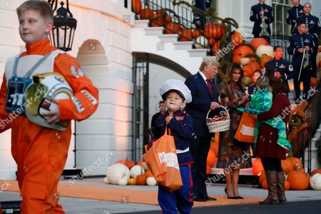 President Donald Trump and first lady Melania Trump give candy to children during a Halloween trick-or-treat event on the South Lawn of the White House which is decorated for Halloween, in Washington