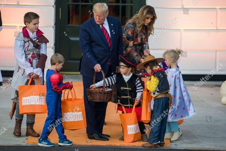 Donald Trump, Melania Trump. President Donald Trump and first lady Melania Trump give candy to children during a Halloween trick-or-treat event on the South Lawn of the White House which is decorated for Halloween, in Washington