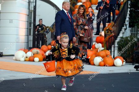 President Donald Trump and first lady Melania Trump watch a young girl as they give candy to children during a Halloween trick-or-treat event on the South Lawn of the White House which is decorated for Halloween, in Washington