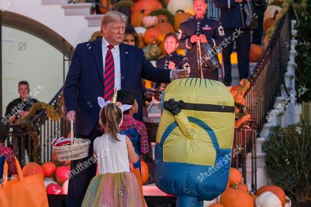 Donald Trump, Melania Trump. President Donald Trump, accompanied by first lady Melania Trump, places a candy bar on the head of child dressed as Minion during a Halloween trick-or-treat event on the South Lawn of the White House which is decorated for Halloween, in Washington