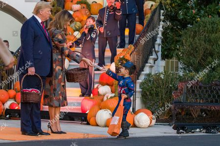 Donald Trump, Melania Trump. President Donald Trump and first lady Melania Trump give candy to child dressed as Captain America during a Halloween trick-or-treat event on the South Lawn of the White House which is decorated for Halloween, in Washington