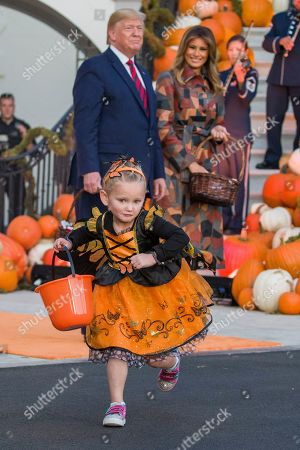 Donald Trump, Melania Trump. A child in costume runs away after getting candy from President Donald Trump and first lady Melania Trump during a Halloween trick-or-treat event on the South Lawn of the White House which is decorated for Halloween, in Washington