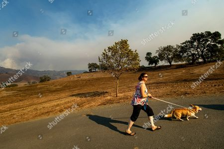 Stephanie LaFranchi climbs a hill to visit the remains of her husband's family home, leveled by the Kincade Fire, in Calistoga, Calif., on . According to Cal Fire, the blaze, burning in the background, has scored more than 66,000 acres and destroyed at least 96 structures