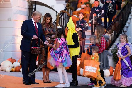US President Donald Trump (L) and First Lady Melania Trump (2-L) hand out candy to children in costumes during a Halloween event at the White House in Washington, DC, USA, 28 October 2019. Halloween is celebrated 31 October.