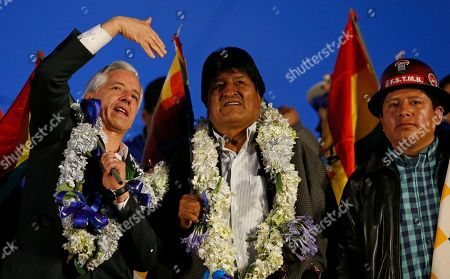 Bolivia's President Evo Morales, center, and Vice President Alvaro Garcia Linera stand before supporters as they celebrate their reelection, as union leader Juan Carlos Guarachi looks on in El Alto, Bolivia, . Morales' backers and foes are blocking streets and highways across the country in a dispute over official election results that show the leftist leader winning reelection without a runoff