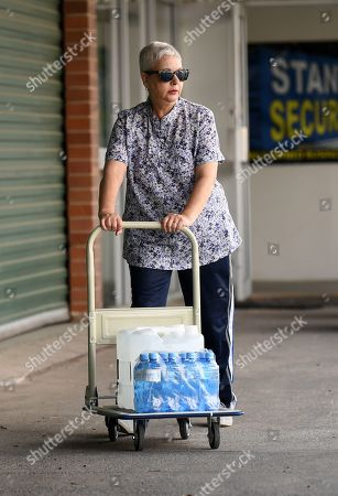 A woman carries water bottles donated by a local charity group in Stanthorpe, Queensland, Australia, 16 October 2019 (issued 29 October 2019). The town of Stanthorpe has been struggling with severe drought and consequential bushfires since September 2019. With the dam's water level down to 25 percent, the town faces an imminent water shortage. Queensland Premier Annastacia Palaszczuk announced in September 2019 a plan to truck in 1.6 million liters of water from a nearby dam to the Storm King Dam, as Stanthorpe is predicted to run out of water by Christmas.