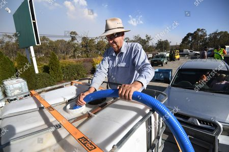Stock Picture of A man collects the water handed out by a local charity group in Stanthorpe, Queensland, Australia, 16 October 2019 (issued 29 October 2019). The town of Stanthorpe has been struggling with severe drought and consequential bushfires since September 2019. With the dam's water level down to 25 percent, the town faces an imminent water shortage. Queensland Premier Annastacia Palaszczuk announced in September 2019 a plan to truck in 1.6 million liters of water from a nearby dam to the Storm King Dam, as Stanthorpe is predicted to run out of water by Christmas.