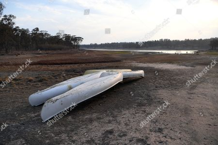 Canoes lie inside the nearly dry reservoir of the Storm King Dam near Stanthorpe, Queensland, Australia, 10 October 2019 (issued 29 October 2019). The town of Stanthorpe has been struggling with severe drought and consequential bushfires since September 2019. With the dam's water level down to 25 percent, the town faces an imminent water shortage. Queensland Premier Annastacia Palaszczuk announced in September 2019 a plan to truck in 1.6 million liters of water from a nearby dam to the Storm King Dam, as Stanthorpe is predicted to run out of water by Christmas.