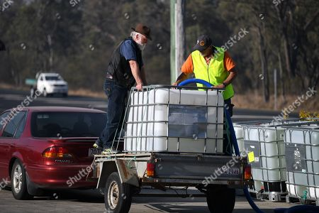 A volunteer (R) from Granite Belt Water Relief charity group fills up a client's water tank in Stanthorpe, Queensland, Australia, 09 October 2019 (issued 29 October 2019). The town of Stanthorpe has been struggling with severe drought and consequential bushfires since September 2019. With the dam's water level down to 25 percent, the town faces an imminent water shortage. Queensland Premier Annastacia Palaszczuk announced in September 2019 a plan to truck in 1.6 million liters of water from a nearby dam to the Storm King Dam, as Stanthorpe is predicted to run out of water by Christmas.