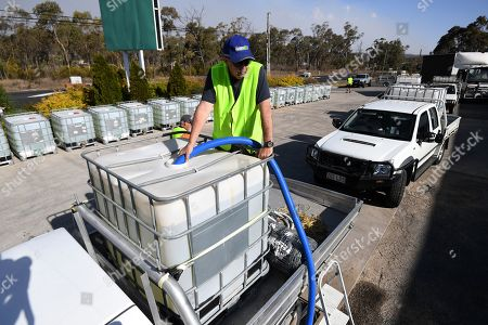 A volunteer from a charity group fills up water tanks in Stanthorpe, Queensland, Australia, 09 October 2019 (issued 29 October 2019). The town of Stanthorpe has been struggling with severe drought and consequential bushfires since September 2019. With the dam's water level down to 25 percent, the town faces an imminent water shortage. Queensland Premier Annastacia Palaszczuk announced in September 2019 a plan to truck in 1.6 million liters of water from a nearby dam to the Storm King Dam, as Stanthorpe is predicted to run out of water by Christmas.