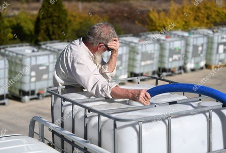 A man fills up a tank with water donated by a local charity group in Stanthorpe, Queensland, Australia, 09 October 2019 (issued 29 October 2019). The town of Stanthorpe has been struggling with severe drought and consequential bushfires since September 2019. With the dam's water level down to 25 percent, the town faces an imminent water shortage. Queensland Premier Annastacia Palaszczuk announced in September 2019 a plan to truck in 1.6 million liters of water from a nearby dam to the Storm King Dam, as Stanthorpe is predicted to run out of water by Christmas.