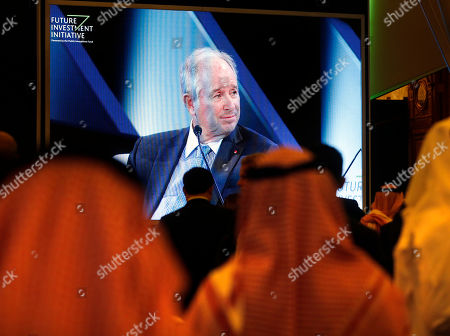 Participants watch Stephen Schwarzman, Chairman and CEO of The Blackstone Group, on a screen at the Future Investment Initiative forum in Riyadh, Saudi Arabia, . The long-planned initial public offering of a sliver of Saudi Arabia's state-run oil giant Saudi Aramco will see shares traded on Riyadh's stock exchange in December, a Saudi-owned satellite news channel reported Tuesday as the kingdom's marquee investment forum got underway