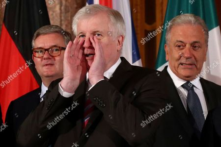 German Interior Minister Horst Seehofer, center, calls his colleague Minister Luciana Lamorgese of Italy prior to a family photo at a meeting of the of the six largest EU countries in Munich, Germany, . In the back ground European Commissioner of Security Sir Julian King, left, and European Commissioner of Migration Dimitris Avramopoulos, right