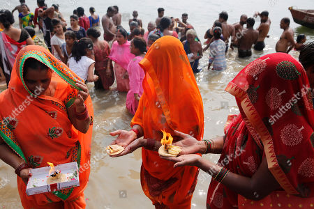 Hindu devotees offers prayers after taking a holy dip in River Yamuna during Bhai Dooj festival in Prayagraj, India, . Bhai Dooj is a festival celebrated by Hindus in north India where sisters mark their love to their brothers by performing rituals which they believe will protect them from evil forces
