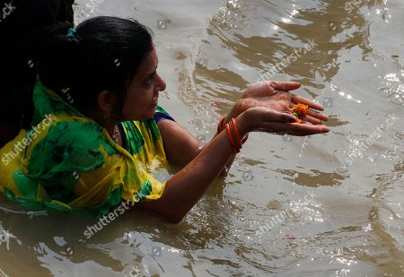 A Hindu woman offers prayers after taking a holy dip in River Yamuna during Bhai Dooj festival in Prayagraj, India, . Bhai Dooj is a festival celebrated by Hindus in north India where sisters mark their love to their brothers by performing rituals which they believe will protect them from evil forces