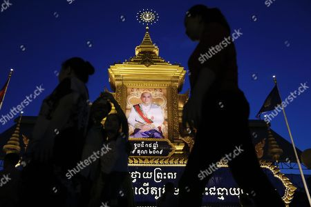 Cambodian people walk past a large portrait of Cambodia's King Norodom Sihamoni, on display in front of the Royal Palace in Phnom Penh, Cambodia, 29 October 2019. Cambodia marks the 15th anniversary of the Coronation Day of King Norodom Sihamoni on 29 October.