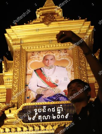 A Cambodian man takes a selfies next to  a large portrait of Cambodia's King Norodom Sihamoni, on display in front of the Royal Palace in Phnom Penh, Cambodia, 29 October 2019. Cambodia marks the 15th anniversary of the Coronation Day of King Norodom Sihamoni on 29 October.