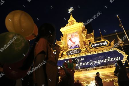 A girl vendor walks past a large portrait of Cambodia's King Norodom Sihamoni, on display in front of the Royal Palace in Phnom Penh, Cambodia, 29 October 2019. Cambodia marks the 15th anniversary of the Coronation Day of King Norodom Sihamoni on 29 October.