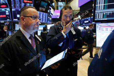 Robert Arciero, Gregory Rowe. Traders Robert Arciero, left, and Gregory Rowe work on the floor of the New York Stock Exchange, . Stocks are off to a slightly lower start on Wall Street as communications and energy companies fall
