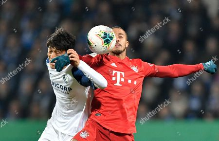 Bayern's Thiago, right, challenges for the ball with Bochum's Chung-Yong Lee during the German soccer cup, DFB Pokal, second round match between VfL Bochum and Bayern Munich at the Vonovia Ruhrstadion stadium, in Bochum, Germany