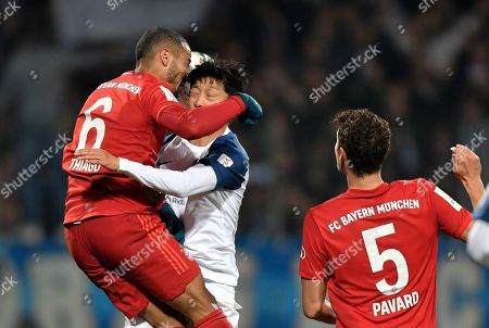 Stock Image of Bayern's Thiago, left, jumps for a header with Bochum's Chung-Yong Lee during the German soccer cup, DFB Pokal, second round match between VfL Bochum and Bayern Munich at the Vonovia Ruhrstadion stadium, in Bochum, Germany