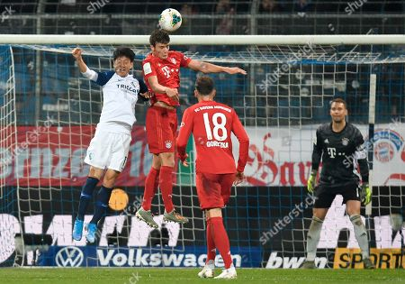 Bayern's Benjamin Pavard, right, jumps for a header with Bochum's Chung-Yong Lee during the German soccer cup, DFB Pokal, second round match between VfL Bochum and Bayern Munich at the Vonovia Ruhrstadion stadium, in Bochum, Germany