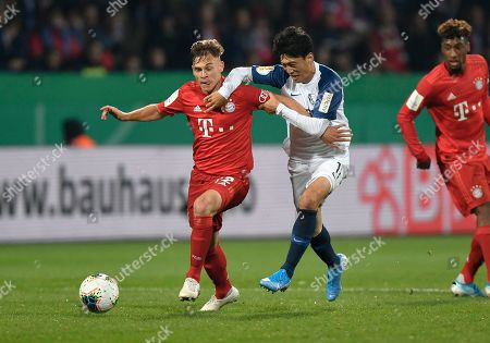 Bayern's Joshua Kimmich, left, challenges for the ball with Bochum's Chung-Yong Lee during the German soccer cup, DFB Pokal, second round match between VfL Bochum and Bayern Munich at the Vonovia Ruhrstadion stadium, in Bochum, Germany