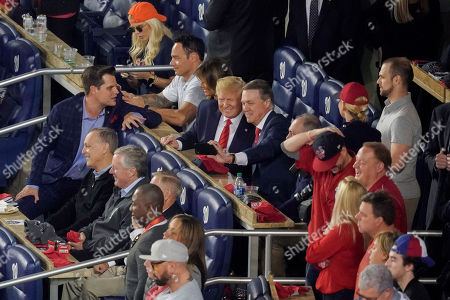 Sen. David Perdue, R-Ga., takes a selfie with President Donald Trump, center, during the seventh inning of Game 5 of the baseball World Series between the Houston Astros and the Washington Nationals, in Washington. Sitting behind Trump is first lady Melania Trump and joining them other Republican lawmakers from l-r., Rep. Matt Gaetz, R-Fla., Rep. Andy Biggs, R-Ariz., Rep. Mark Meadows, R-NC., and Sen. Lindsey Graham, R-S.C