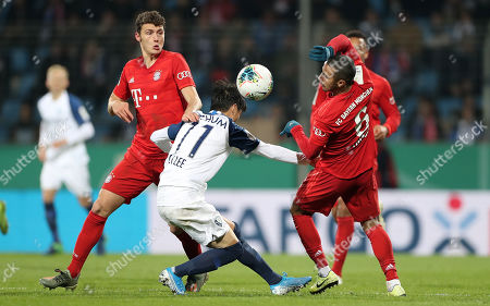 Bayern's Benjamin Pavard (L) and Bayern's Thiago (R) in action against Bochum's Chung Yong Lee (C) during the German DFB Cup second round soccer match between VfL Bochum and FC Bayern Muenchen in Bochum, Germany, 29 October 2019.