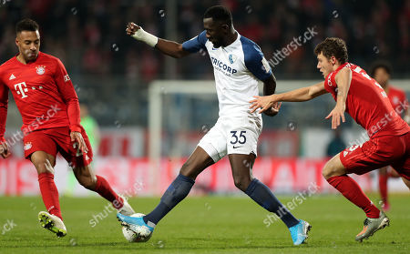 Stock Image of Bochum's Silvere Ganvoula (C) in action against Bayern's Benjamin Pavard (R) and Bayern's Corentin Tolisso (L) during the German DFB Cup second round soccer match between VfL Bochum and FC Bayern Muenchen in Bochum, Germany, 29 October 2019.