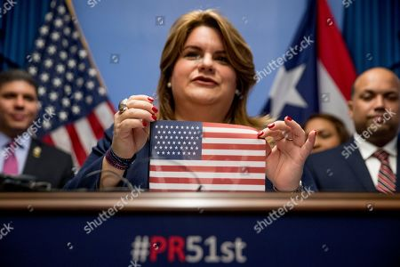 Resident Commissioner Jenniffer Gonzalez-Colon, who represents Puerto Rico as a nonvoting member of Congress, holds up an American flag with 51 stars, speaks about Puerto Rico statehood during a news conference on Capitol Hill in Washington