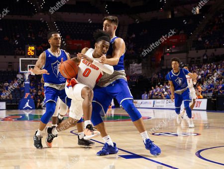 Stock Photo of Ques Glover, Darius Moore, Hunter Parrish. Florida guard Ques Glover (0) drives past Lynn guard Darius Moore, left, and forward Hunter Parrish during the second half of an NCAA college basketball exhibition game, in Gainesville, Fla
