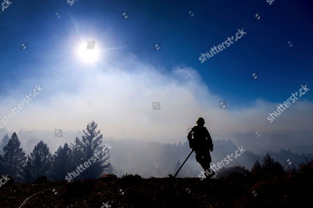 Firefighter Josh Petrell monitors the Kincade Fire burning near Healdsburg, Calif., on . The overall weather picture in northern areas is improving as powerful, dry winds bring extreme fire weather to Southern California