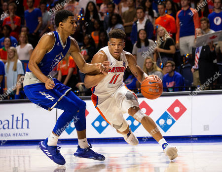 Stock Image of Keyontae Johnson, Cameron Gaines. Florida forward Keyontae Johnson (11) drives around Lynn forward Cameron Gaines (12) during the second half of an NCAA college basketball exhibition game, in Gainesville, Fla