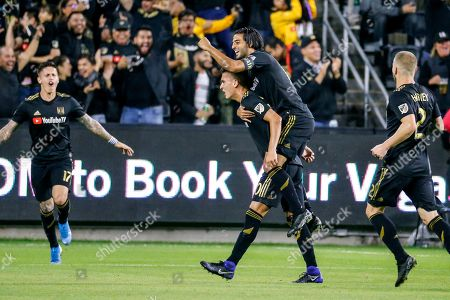 Los Angeles FC midfielder Eduard Atuesta, second from left, celebrates his goal with forward Carlos Vela, second from right, during the first half of the team's MLS soccer Western Conference final against the Seattle Sounders, in Los Angeles
