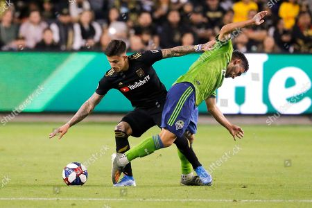 Los Angeles FC forward Brian Rodriguez, left, vies with Seattle Sounders midfielder Cristian Roldan for the ball during the first half of the MLS soccer Western Conference final, in Los Angeles