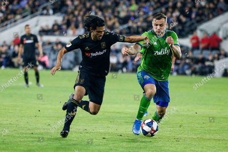 Los Angeles FC forward Carlos Vela, left, vies against Seattle Sounders forward Jordan Morris during the second half of the MLS soccer Western Conference final, in Los Angeles. The Sounders won 3-1